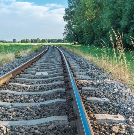 Gebogen enkel spoor spoorweg in een landelijke omgeving.
