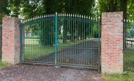 Green wrought iron gate between two masonry brick pillars photo