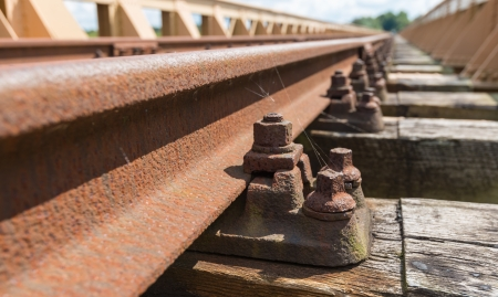 Rusty rails, clamps and wooden sleepers at an historic Dutch railway bridge  photo