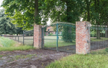 Green wrought iron gate and two masonry brick pillars before a large estate in Belgium.