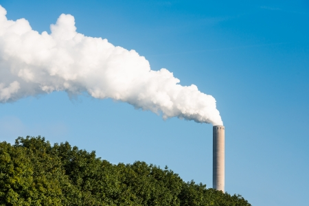 White smoke and steam from a high chimney of a power plant against a bright blue sky and above concealing trees  photo