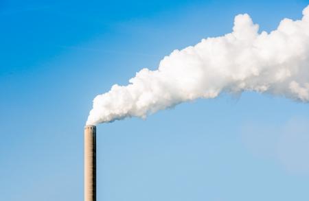 Weiß Dampf und Rauch von einem sehr hohen Schornstein auf einem hellen sonnigen Tag emittiert