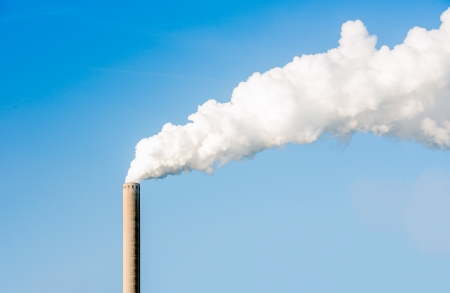 White steam and smoke emitted from a very high chimney on a bright sunny day  Stock Photo