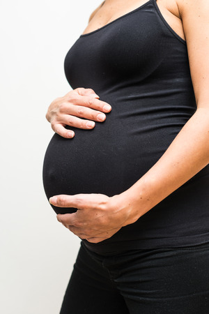 nine months: Nearly nine months pregnant woman holds her large belly with both hands.