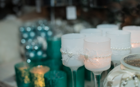 Closeup of burning candles in glasses decorated with hearts and pearls. photo