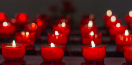 Tea candles in red glass holders burning atmospheric in a small Dutch chapel  photo