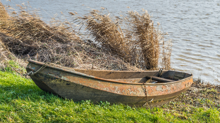 chipped paint: The surface of this neglected rowing boat is rusted and has chipped paint. Stock Photo