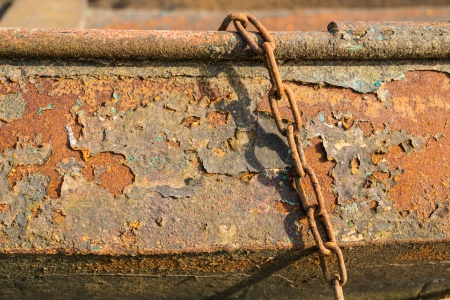 chipped paint: Rusted surface of an iron rowing boat with chipped paint  layers in autumnal sunlight. Stock Photo