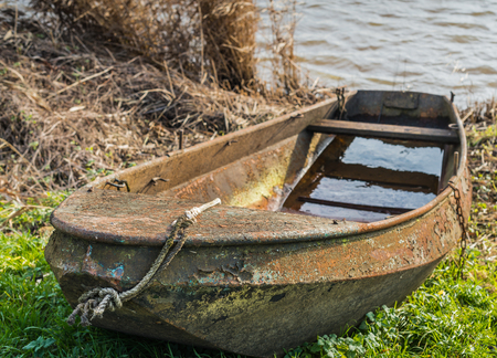 Neglected rusted rowing boat on the banks of a lake and partially filled with water. photo