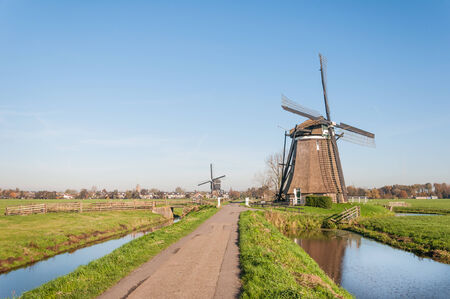 Typical Dutch polder landscape with two historic windmills in the green polder area and the edge of a small village in the background. photo