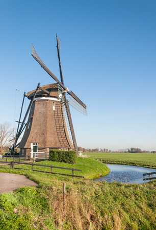 Typical Dutch polder landscape with two windmills in the green polder area and the edge of a small village in the background. photo