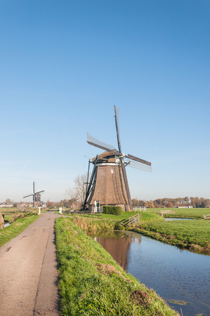 polder: Typical Dutch polder landscape with two windmills in the green polder area and the edge of a small village in the background. Stock Photo
