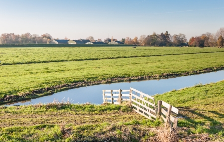 Typical Dutch landscape with a wooden fence and a ditch in the foreground and green grassland and the edge of a small village in the background. photo