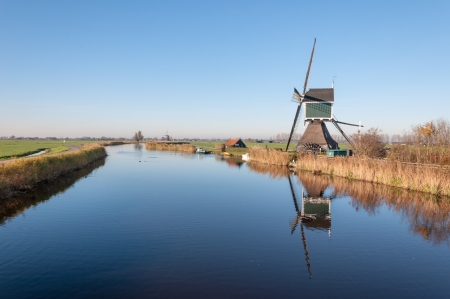 polder: Dutch polder landscape in autumn with an old windmill with scoopwheel next to a small river. Stock Photo