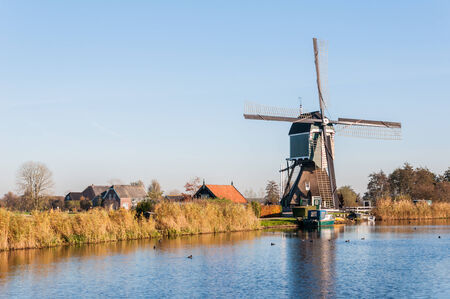 Picturesque and colorful polder landscape in the Netherlands with an historic windmill next to water. photo