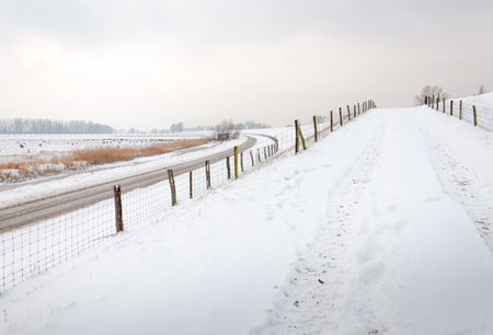 Snow-covered driveway to a dike, a country road and fences with mesh and wooden poles. photo