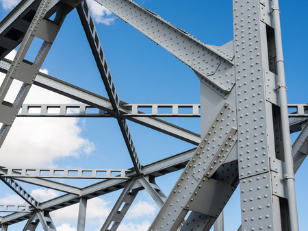 Detail shot of an historic gray painted Dutch riveted truss bridge against a blue sky. Stockfoto