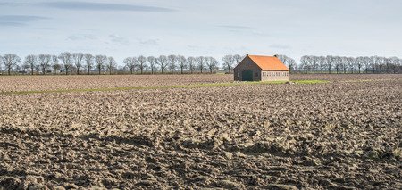 Old barn of brick masonry with an orange tiled roof in a large plowed field at the end of the winter season in the Netherlands. photo