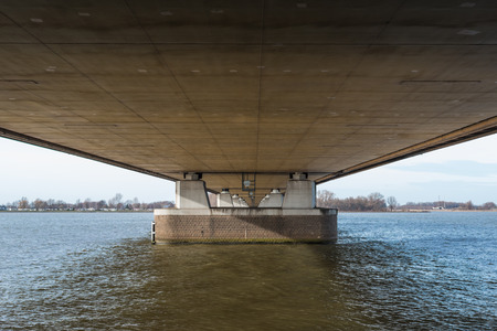 Bottom of a long road bridge over a wide river in the Netherlands. photo