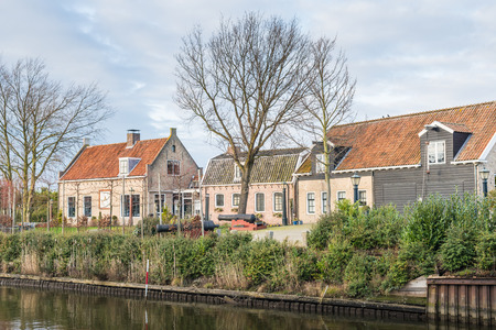 Picturesque houses situated on the waters of an old fortified city in the Netherlands. The shot is taken at the end of a sunny winter day.