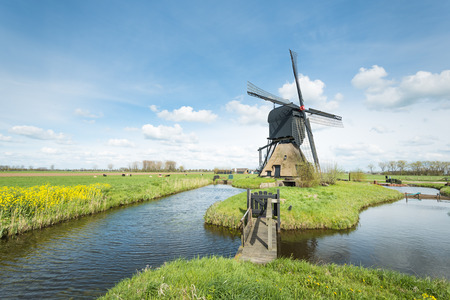 Historic windmill in the Netherlands on a sunny day in the spring season. photo
