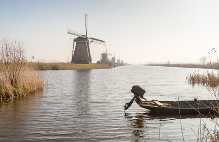 In the foreground a small boat with an outboard motor in the water and in the background a row of Dutch windmills  photo