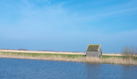 Old barn with a plastered wall and mossy tiles along a the water of a canal in a Dutch polder landscape. photo