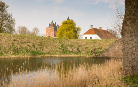 rampart: Medieval castle and a white building behind the high rampart and moat at the beginning of spring.