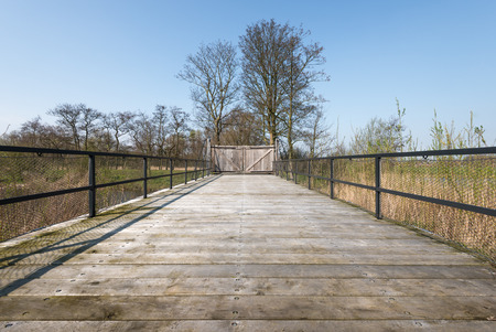 Closed wooden gate at the end of a long wooden bridge with a steel balustrade equipped with mesh screen. photo