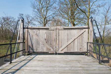 Closed wooden gate at a wooden bridge with a steel balustrade equipped with mesh screen. photo