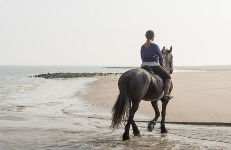 Jonge vrouw rijdt op een paard door het water aan de rand van het strand