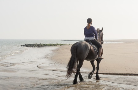 Young woman riding on horseback through the water at the edge of the beach