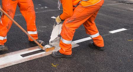 Close-up affixing line marking  on the asphalt road surface