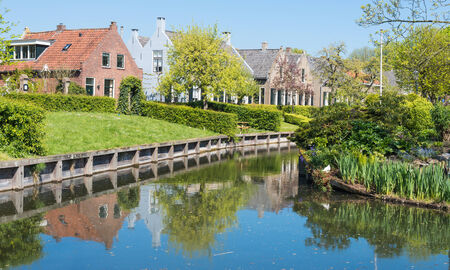drimmelen: Houses in the historic Dutch village of Drimmelen reflected in the mirror smooth water surface of the canal.