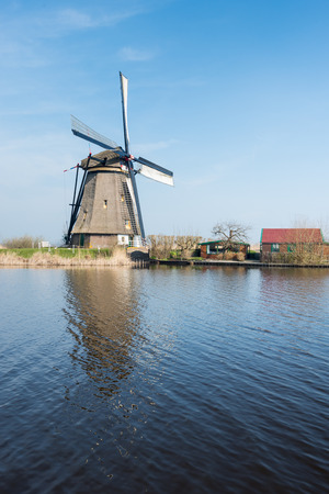 Old thatched polder mill near the Dutch village of Kinderdijk on a sunny spring day. photo