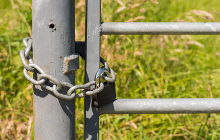 padlocked: Closed galvanized steel gate locked with an iron chain and a padlock