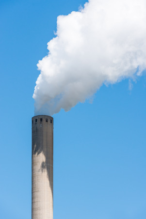Closeup of a bright blue sky with white polluting smoke from a high chimney  photo