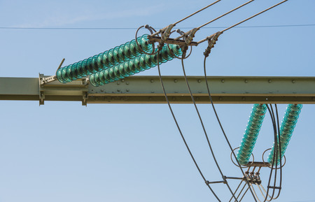 insulators: Closeup of high voltage lines, insulators and a small part of a power pylon against a blue sky on a sunny day  Stock Photo