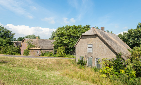 Abandoned and neglected historic farmhouse down a Dutch embankment  photo