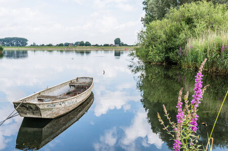 Weathered steel rowing boat perfectly reflected in the mirror smooth water surface of a Dutch river  photo