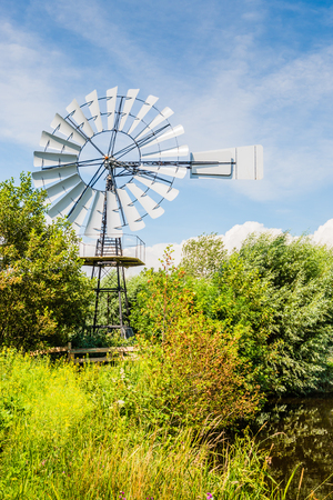 Wind powered multi-bladed water pump built in a German factory and since 1922 working as a water mill in a Dutch polder area. photo