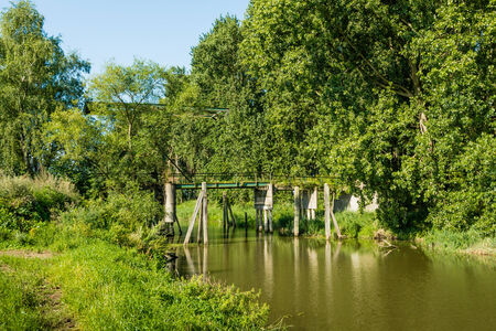 draw bridge: Neglected drawbridge over a narrow stream overgrown with bushes and plants