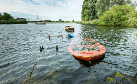 sunk: Submerged orange rowing boat near the banks of river