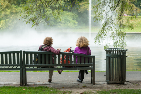 Two women lost in their thoughts stare to the fountain in the park sitting on a wooden bench beside a dustbin. photo