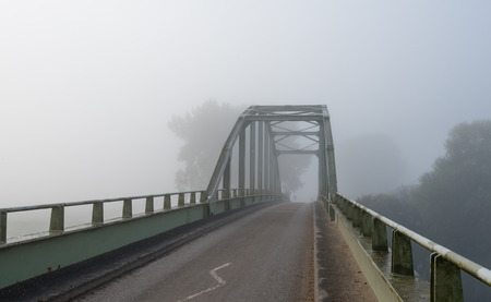 An old steel arch bridge on a foggy morning in early autumn season. photo