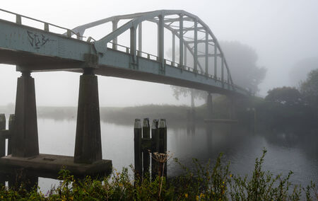 steel arch bridge: Steel arch bridge over a small river on a foggy morning early in the autumn season Stock Photo