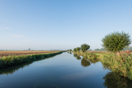 Colorful landscape in the fall season with agricultural fields and a  stream with a mirror smooth water surface.