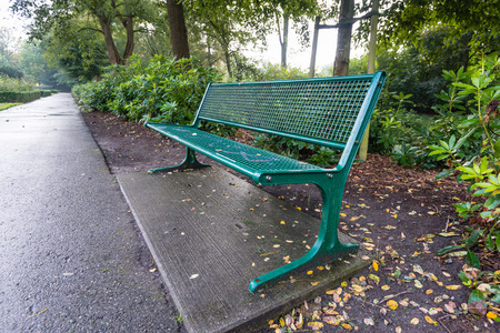 Green painted steel bench situated next to a path in a Dutch park. photo