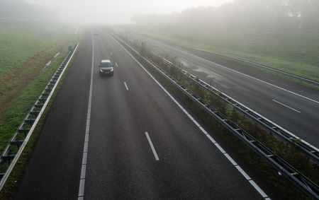 guardrail: Passenger cars with burning headlights driving on a freeway in the Netherlands early on a foggy morning in the fall season.