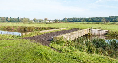 squashy: Swampy cattle bridge across a narrow river in a rural area with a backdrop the outline of a small Dutch village. Stock Photo
